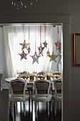 Gedeckter Weihnachtstisch unter hängenden Weihnachtssternen