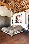 Bedroom below exposed roof structure and double bed below pictures on wall