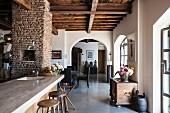 View past kitchen counter into open-plan living area with arched open doorway in renovated country house with rustic wood-beamed ceiling