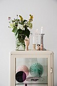 Bouquet in glass vase next to lit candles in candlesticks on retro display case with honeycomb paper balls on glass shelf