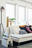 Magazine rack and designer standard lamp next to many cushions on pale couch below window