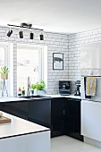 U-shaped kitchen counter with black cabinets against white-tiled wall and spotlights on rail mounted on ceiling