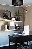 Schreibtisch aus dunklem Holz mit Notebook auf Gestell, im Hintergrund Büroutensilien auf weissen Regalkonsolen an hellbraun getönter Wand