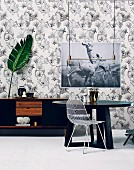 Modern dining room with graphic elements in black and white: round dining table and sideboar against a pattern wallpaper