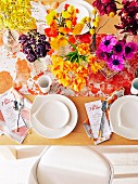 Laid table with lavish floral decorations in yellow and red tones, menu cards and speckled table runner