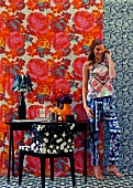 Young woman in room with different patterns on wallpaper, carpet, armchair and clothes