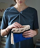A woman holding a knooked clutch bag – knitting with a hook