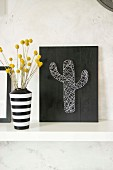 String art picture of cactus and black and white stripes vase of dried flowers