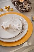 Teller mit Schneekristallen als Deko auf goldenem Platzteller