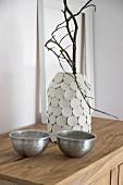 Zweig in selbst gestalteter Vase aus Einmachglas mit Plättchen aus Modelliermasse, davor zwei Schälchen
