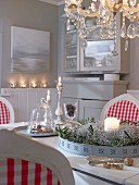 Gingham chairs, chandeliers and candlelight in wintry, decorated dining room