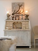 Two candle lanterns on stone bases on bureau decorated for winter