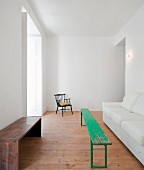 Interior with green-painted bench between wooden bench and white sofa