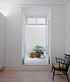 Retro chair with green scatter cushion in minimalist interior in front of open French window with view into courtyard