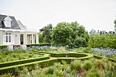 Geometric gardens with clipped hedges and elegant country house in background