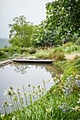 Idyllischer Teich mit Holzsteg in Gartenanlage