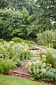 Geschwungener Natursteinweg in grüner Gartenanlage