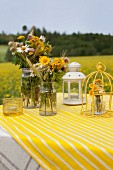 Colourful bouquets of wildflowers in vintage jars, ornamental bird cage and lantern on yellow and white striped tablecloth outdoors