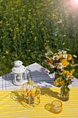 Laterne, Dekokäfig und Wiesenblumensträusse auf gelbweiss gestreiftem Tischtuch in Freiem