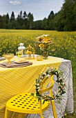 Wreath of flowers on yellow metal chair next to table set in yellow colour scheme with field of flowering rapeseed in background
