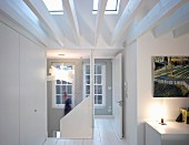 Bright, attic hallway with white, wooden beams below skylights and open door leading to stairwell
