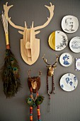 Decorative wall plates and various hunting trophies on dark grey wall