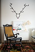 Antique Scandinavian rocking chair in front of metal cabinet below stylised stag's head made from black washi tape on white wall