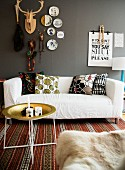 Tray table, white sofa with patterned scatter cushions on rug below decorations on grey wall