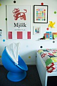 Blauer Kinderstuhl mit Halbschalensitz neben Bett mit buntem Bezug, an Wand bunte Punkten und Plakaten