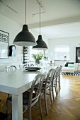 Retro pendant lamps above white-painted table and wooden chairs in open-plan living area