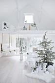 weiße Weihnachtsdekoration mit Tannenbaum und Zweigen in weißem Ambiente