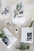 White-wrapped Christmas gifts decorated with evergreen sprigs and photos