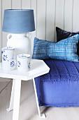 Blau-weiße Tischlampe auf einem Beistelltisch neben Bodenkissen