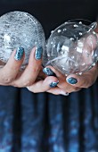 Glass Christmas baubles held in hands with glittery nails