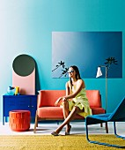 Young woman on orange sofa in front of turquoise wall