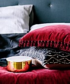 Cushions with red velvet cover and tassels and with black and white cover next to shiny gold lid box