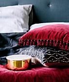 Kissen mit rotem Samtbezug und Quasten und mit schwarz-weißem Bezug neben goldglänzender Deckeldose