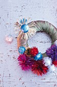 A wreath being decorated with chocolate suns and glittery pompoms