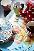 Coffee crockery and a painted porcelain sugar pot on a tray with a retro picture