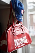 Red sports bag and blue cap hanging from peg