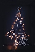 A Christmas tree drawn in chalk on a blackboard with fairy lights and baubles
