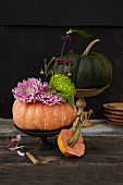Autumnal pumpkin decoration with asters and chrysanthemums