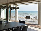 View over dark dining table with matching chairs to terrace and open sea