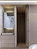 Washstand with drawers in base unit and mirror built into niche with indirect lighting; open door leading to toilet area