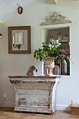 Leafy branches in antique planter on top of vintage console table with peeling paint between niche in wall and candle sconce in empty picture frame