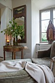 Chaise longue in front of window with religious statue on windowsill next to candlesticks on Biedermeier side table