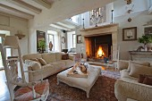 Pale sofa set and ottoman in front of fire in large fireplace in grand country house