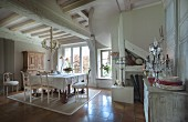 White dining set next to window and crockery and opulent candelabra on top of cabinet in open-plan interior of traditional country house