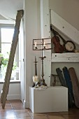 Lit candles in candle holders on antique music stand on platform with various old musical instruments in niche to one side