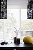 Black pendant lights over dining table in front of balcony window